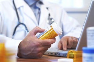 Doctor looking at bottle of prescription pills. Pharmaceutical liability attorney Baltimore Maryland
