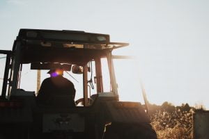 Farmer riding a tractor into the sunset